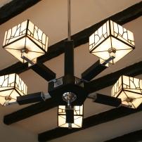 """Pièce d'exception, Pentalight est un élégant lustre ancien Art Déco de 1930 entièrement rénové et électrifié. Le coupoles rondes initiales, """"vieillotes"""" et sans caractère ont été remplacées pas 5 coupoles carrées d'aspect à la fois moderne et rétro, en vitrail Tiffany composées de 240 pièces de verre blanc nacré et opalescent. D'une taille imposante (hauteur 82 cm, diamètre 70 cm), ce lustre apportera suffisamment de luminosité à votre intérieur, s'il s'agit d'une salle à manger ou d'une cuisine, sans """"l'agressivité"""" des luminaires traditionnellement choisis pour ces pièces, et diffusera une lumière chaleureuse, profonde et indirecte. Les 5 branches de Pentalight sont composées de pièces en inox et en bois teinté en noir mat."""