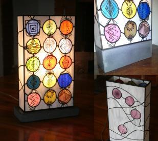 """Lampe contemporaine """"Signes"""" en vitrail Tiffany constituée de verres opalescents de couleurs multiples. Dessins représentant des signes """"naïfs"""" peints à la grisaille et cuits à 650 °. Taille hauteur 39 cm largeur 23 cm épaisseur 11 cm. Socle en béton ciré gris anthracite lui assurant un aspect très moderne et une grande stabilité."""