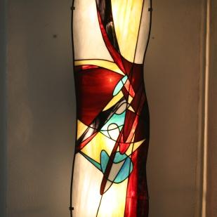 Ethna est une imposante applique murale en vitrail Tiffany (hauteur 95 cm, largeur 26 cm). Les verres, opalescents et de couleur blanche, ocre clair, violets foncés et noirs, rouge très foncé et bleu outremer donneront à votre intérieur une ambiance à la fois lumineuse, chaleureuse et originale (les photos ne rendent vraiment pas justice à sa luminosité : difficile de photographier la lumière et la transparence...). Le panneau est réversible selon votre préférence pour des verres d'un côté lisses ou de l'autre côté, structurés. Ethna est montée sur une structure électrifiée en acier blanc (fournie), équipée de 2 encoches de suspension pour un accrochage aisé sur un mur.