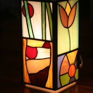 """Lampe """"Naïve"""" contemporaine en vitrail Tiffany. Ses représentations figuratives naïves confèrent à cette lampe une allure très gaie, lumineuse et très colorée. Elle est constituée de verres opalescents multicouleurs."""