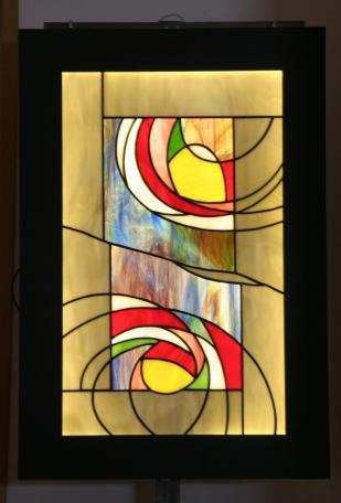 """Tableau lumineux, pour faire de la lumière un élément esthétique autant qu'un mode d'éclairage, appelé """"Nénuphar"""" constitué de verres opalescents montés en vitrail Tiffany de différentes couleurs (contour gris perle foncé, fond au centre violet/bleu/vert, motifs rouge, vert, bleu, blanc, rose, vert, violet foncé et marron) dans une structure cadre acier. Le rétro-éclairage à Leds inséré dans la structure acier assure un éclairage d'ambiance extrèmement doux. Accroché à votre mur à la manière d'un tableau à l'aide de ses crochets de suspension, """"Nénuphar"""" peut aussi être posé sur un meuble, contre un mur ou encore sur un chevalet. Dans tous les cas, il vous assurera une ambiance lumineuse et ne passera pas inaperçu, qu'il soit allumé..... ou éteint.... Largeur 45 cm Hauteur 67 cm Epaisseur 2,5 cm Poids 8 kg"""