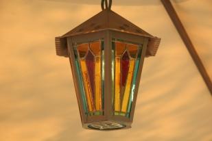Lanterne de jardin en fer forgé de couleur rouille ornée de 6 panneaux de vitrail Tiffany + 1 sur le fond de couleur rouge, turquoise et jaune foncé. Hauteur 35 cm (hors chaîne), largeur 26 cm. peut-être installée en extérieur à l'abri de la pluie