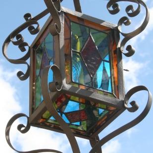 Renaissance d'une ancienne et très grande lanterne de jardin (63 cm de h.) en fer forgé gris acier ornée de 6 panneaux de vitraux Tiffany de couleur rouge, bleu turquoise et jaune foncé. Hauteur 63 cm Largeur 26 cm Profondeur 26 cm. Petite porte avec clef pour changer l'ampoule