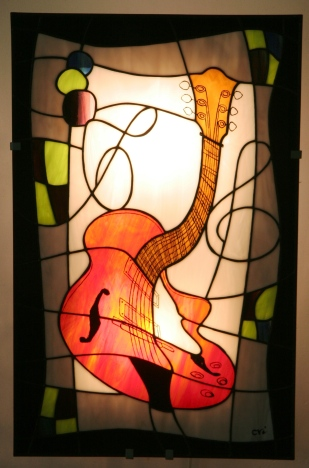 Applique murale vitrail Tiffany représentant une guitare stylisée, verre opalescent blanc pour le fond, rouge vif orangé strié de jaune pour la guitare, noir pour le pourtour, et vert anis et violet pour les motifs. Les détails du type cordes, tête, clefs, chevalet... sont peints à la grisaille et cuits à 650° dans la tradition du vitrail. Guitare est montée sur une structure électrifiée en acier blanc, équipée de 2 encoches de suspension pour un accrochage aisé sur un mur. Hauteur 55 cm Largeur 35 cm. Epaisseur hors tout mur-panneau : 9 cm. Assure un éclairage doux, pour une ambiance lumineuse et chaleureuse.