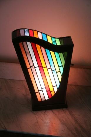 Lampe Harpège en vitrail Tiffany. Evoquant une harpe. Verres opalescents multi-couleurs. Socle en noyer massif teinté noir Napoléon.