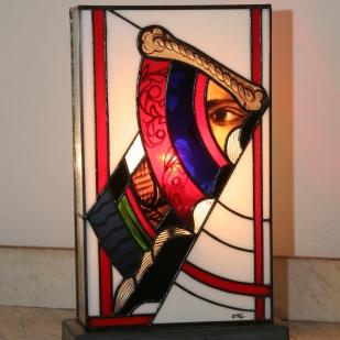 Lampe Newold-one en vitrail Tiffany très contemporaine. Innovant et original : alliance de l'ancien et du moderne, cette grande lampe (37 cm) est constituée de verres opalescents blanc, rouge, strié transparent et noir très contemporains et de verres issus de vitraux datant de 1843 d'une ancienne abbaye. Au dos de la lampe on retrouvre la signature du maître verrier ayant réalisé les vitraux en 1843. Socle en béton ciré gris anthracite renforçant sa modernité et lui assurant une grande stabilité. Hauteur 37 cm, Largeur 23 cm, Profondeur 11 cm