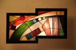 Nineleven : applique murale vitrail Tiffany, verres opalescents. Montée sur structure électrifiée en acier blanc. Hauteur 26 cm, largeur 56 cm.