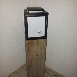 """Lanterne de jardin """"Stéphanie"""" en fer forgé sur socle bois. Chaque panneau de verre blanc porte l'intiale d'un des membres de la famille"""