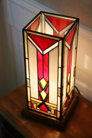 Lampe Art Déco en vitrail Tiffany forme colonne. Verres opalescent blanc, rouge, vert et jaune lumineux et profond. Socle en noyer massif doré.