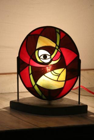 Lampe Eyo contemporaine en vitrail Tiffany. Cette lampe est constituée de verres opalescents multicouleurs. Socle en béton ciré gris anthracite lui assurant un aspect très moderne et une grande stabilité. Hauteur 30 cm, Largeur 27 cm, Profondeur 13 cm