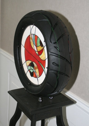 """ORIGINAL, EXCLUSIF et ANTICONFORMISTE !!! Ou comment prouver un nouvelle fois que le vitrail trouve sa place """"où on veut, comme on veut....."""" Découvrez Bibenlight.... et cédez à la fantaisie de cette pièce d'un esthétisme surprenant. Cette lampe design et très contemporaine est tout simplement faite d'un pneu à l'intérieur duquel un vitrail Tiffany a été inséré. Des petits pieds fixés sous le pneu lui permettent d'être posée soit directement sur le sol soit sur un meuble ou le support de votre choix. L'éclairage est assuré par une bande de Leds pour un éclairage discret et lumineux mais aussi très économique (3 W), donnant à cette lampe une originalité sans pareil. Diamètre 44 cm Hauteur sur pieds 46 cm Prof. 13 cm"""