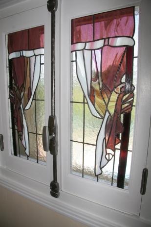 Vitraux Tiffany insérés dans petite fenêtre. Motif simulant des rideaux drapés