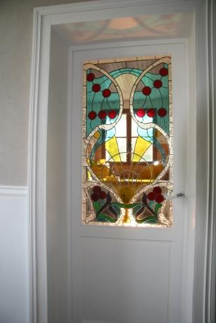 Panneaux de vitraux insérés dans une porte. Une porte pleine a été évidée pour laisser passer la lumière mais occulter la vue. Vitrail reprenant les codes de l'Art Nouveau