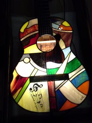 """7ème exercice de style autour de l'instrument de musique : une guitare d'apprentissage qui a rempli son office et entame une seconde vie en devenant un objet de décoration original. Ce modèle a été spécialement conçu avec une dédicace personnalisée pour un anniversaire. Elle peut trôner avec fierté dans votre salon ou votre salle de musique !!! Chaque modèle est original et unique : les couleurs et le dessin du panneau de vitrail sont toujours différents, mais aussi le caisson qui, pour ce modèle, est couleur noyer doré. Pièce d'exception : extrême originalité, design, élégance mais aussi """"fun"""" pour cette guitare électrifiée pouvant être posée au sol, sur un meuble ou suspendue au mur. Cadeau idéal pour un mélomane. Caisson d'une guitare véritable en bois dont le panneau avant a été remplacé par un panneau de vitrail constitué de verres opalescents vous garantissant un éclairage d'ambiance doux, chaleureux et très lumineux. Les verres sont multicolores : bleu pétrole, bleu cobalt..., blanc, différents rouges très lumineux et vifs, différents verts, violet, parme, orange, jaune, brun, translucides.... choisis pour leur particularité de structure. Quelques-uns d'entre eux étant peints à la grisaille (peinture pour verre cuite à 650 degrés). Le tout étant extrèmement lumineux : la photo ne rend pas hommage à cette particularité (difficile de photographier la lumière....)."""