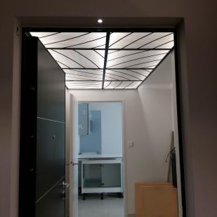 Plafond lumineux posé dans une structure acier. Rétro-éclairé, il est composé de 8 panneaux de 67*62 cm pour une longueur totale de 260*140 cm. Vitrail au plomb armé et verre opalescent blanc
