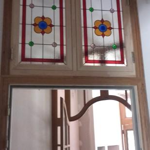 Panneaux de vitraux Tiffany insérés en imposte dans une menuiserie