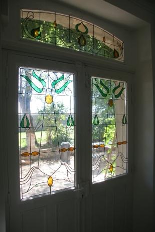 Panneaux de vitraux insérés dans un double vitrage, dans une porte d'entrée. Une porte pleine a été évidée pour laisser passer la lumière. Vitrail reprenant les codes de l'Art Nouveau