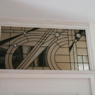 Vitrail Tiffany posé en imposte. Style contemporain reprenant les codes de l'Art Déco. Verres translucides de différentes structures, verre noir et cabochons transparents