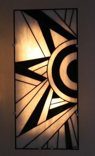 """""""Ycara"""" est une applique murale en vitrail Tiffany (hauteur 56 cm, largeur 26 cm). Son dessin s'inspirant de la géométrie cubiste donne à cette applique son modernisme mais aussi son style intemporel inspiré de l'Art Déco. Les verres, opalescents et de couleur Blanc nacré et Noir donneront à votre intérieur une ambiance à la fois lumineuse et chaleureuse. """"Ycara"""" est constituée de 38 pièces de verre montées en vitrail Tiffany, et les soudures, à l'étain, ont été patinées en noir pour un aspect ancien. Elle est montée sur une structure électrifiée en acier blanc (fournie), équipée de 2 encoches de suspension pour un accrochage aisé sur un mur disposant d'une arrivée électrique."""