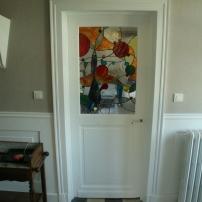 Panneaux de vitraux insérés dans une porte. Une porte pleine a été évidée pour laisser passer la lumière mais occulter la vue. Vitrail donnant sur une buanderie et évoquant le milieu aquatique avec des verres structurés de vagues, des galets et des poissons stylisés