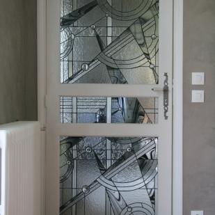 Vitrail Tiffany de plus de 400 pièces de verres. Inséré dans une porte dont 3 parties ont été évidées. Style contemporain reprenant les codes de l'Art Déco. Verres translucides de différentes structures, verre noir et cabochons transparents
