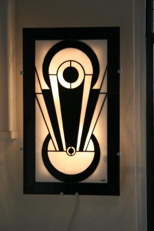 """""""Tamara"""" est une applique murale en vitrail Tiffany (hauteur 56 cm, largeur 34 cm). Son dessin s'inspirant de la géométrie cubiste donne à cette applique son modernisme mais aussi son style intemporel inspiré de l'Art Déco. Les verres, opalescents et de couleur Blanc nacré et Noir donneront à votre intérieur une ambiance à la fois lumineuse et chaleureuse. """"Tamara"""" est constituée de 43 pièces de verre montées en vitrail Tiffany, et les soudures, à l'étain, ont été patinées en noir pour un aspect ancien. Elle est montée sur une structure électrifiée en acier blanc (fournie), équipée de 2 encoches de suspension pour un accrochage aisé sur un mur disposant d'une arrivée électrique."""