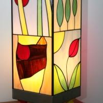 """Originale et Unique : """"Candide"""" est une très grande Lampe (52 cm) d'Art Naïf Contemporain en Vitrail Tiffany. Les verres sont opalescents et multicolores (bleus, rouges, oranges, noir, violets, jaunes, verts, marrons....). Très vive, gaie, colorée et lumineuse, cette lampe est constituée d'un socle en inox brossé monté sur 4 pieds de bois peint vert, rouge, bleu et jaune pour renforcer son côté ludique et joyeux. Les 4 faces sont toutes différentes et faites pour chacune d'entre elles de 2 scènes naïves stylisées et très colorées en véritable vitrail Tiffany."""