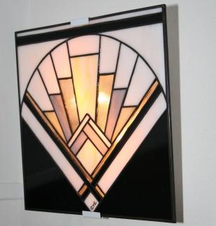 """""""Evora"""" est une applique murale en vitrail Tiffany (dimensions 29 x 29 cm) d'inspiration Art Déco. Les verres, opalescents et de couleurs Blanc nacré, Noir, Transparent ciselé, Gris perle et Jaune pâle donneront à votre intérieur une ambiance à la fois lumineuse et chaleureuse.""""Evora"""" est constituée de 35 pièces de verre montées en vitrail Tiffany, et les soudures, à l'étain, ont été patinées en noir pour un aspect ancien. Elle est montée sur une structure électrifiée en acier blanc (fournie), équipée de 2 encoches de suspension pour un accrochage aisé sur un mur disposant d'une arrivée électrique."""