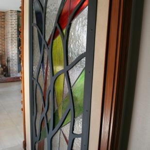 Très grand panneau de vitrail '115*220 monté au plomb traditionnel et armé. Il est inséré dans 2 structures acier identiques posées de part et d'autre et qui ont été découpées pour évoquer des branches d'arbre. Très coloré, les verres sont translucides pour laisser passer la lumière entre une entrée et un bureau mais en occulter la vue