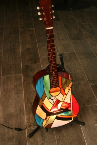 """6ème exercice de style autour de l'instrument de musique : une guitare d'apprentissage qui a rempli son office et entame une seconde vie en devenant un objet de décoration original. Elle peut trôner avec fierté dans votre salon ou votre salle de musique !!! Chaque modèle est original et unique : les couleurs et le dessin du panneau de vitrail sont toujours différents, mais aussi le caisson qui, pour ce modèle, est couleur noyer doré. Pièce d'exception : extrême originalité, design, élégance mais aussi """"fun"""" pour cette guitare électrifiée pouvant être posée au sol, sur un meuble ou suspendue au mur. Cadeau idéal pour un mélomane. Caisson d'une guitare véritable en bois dont le panneau avant a été remplacé par un panneau de vitrail constitué de verres opalescents vous garantissant un éclairage d'ambiance doux, chaleureux et très lumineux. Les verres sont multicolores : bleu pétrole, bleu cobalt..., blanc, différents rouges très lumineux et vifs, différents verts, violet, parme, orange, jaune, brun, translucides.... choisis pour leur particularité de structure. Quelques-uns d'entre eux étant peints à la grisaille (peinture pour verre cuite à 650 degrés). Le tout étant extrèmement lumineux : la photo ne rend pas hommage à cette particularité (difficile de photographier la lumière....)."""