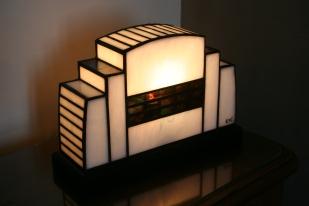 1930 est une lampe de style Art Déco en véritable Vitrail Tiffany. Verres opalescents Blanc pur et violet strié de vert, de bleu, de rouge et de jaune. Soudures patinées noires. Socle en frêne massif teinté noir Napoléon patine finition antiquaire