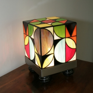 """Originale et Unique : Lampe Art Contemporain """"LE Kube Seventies"""" de Style Années 70 en Vitrail Tiffany multicolore (bleu turquoise, rouge, orange, noir, blanc, violet, jaune, vert et marron). Très vive, gaie, colorée et lumineuse, cette lampe est constituée d'un socle en inox brossé monté sur 4 pieds de résine noire filetée de blanc."""